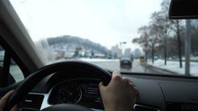 Close-up As mãos das mulheres conduzem o carro Fora da janela é uma cidade do inverno 4K mo lento vídeos de arquivo