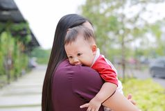 Close-up Asian baby boy lying in hug of mother. Close-up Asian baby boy lying in hug of mother royalty free stock image
