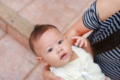 Close-up Asian baby boy lying in hug of mother with looking camera.  stock images