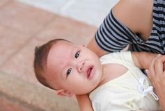 Close-up Asian baby boy lying in hug of mother with looking camera.  royalty free stock photo