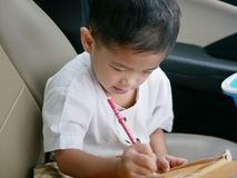 Asian baby writing on a cardboard box while sitting in a car waiting for her mother to do some errands royalty free stock photos