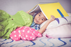 Close up. Asian boy covering head with book and smiling. Educati Stock Photo