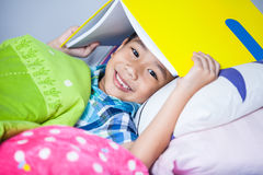 Close up. Asian boy covering head with book and smiling. Educati Royalty Free Stock Image