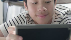 Close up of Asian boy playing on tablet. stock video