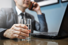 Close up Asian Businessman in grey suit holding glass of water. Royalty Free Stock Photo