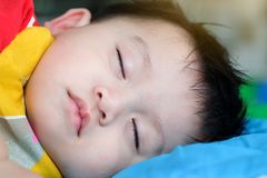 Asian child boy is sleeping on bed royalty free stock photos