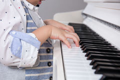 Close up of Asian Chinese little boy`s hand on piano. Keyboard Royalty Free Stock Image