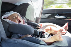Close Up Asian cute newborn baby sitting in modern car seat. Child new born traveling safety on the road. Safe way to travel fastened seat belts in a vehicle stock images