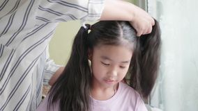Asian family with mother combing her little girl. Close up Asian family with mother doing daughter`s hair stock footage