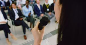 Female speaker speaks in a business seminar 4k. Close-up of Asian female speaker speaks in a business seminar. She is holding a microphone 4k stock footage