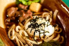 Close up traditional menu, Korea noodles with pork soup and egg and white sesame seeds topping, tasty menu for lunch. Close up Asian food, Korea noodles with stock photo