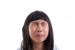 Close up Asian girl in pajamas crying on white. Royalty Free Stock Image