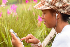 Close up of Asian girl playing internet and listening music from mobile phone in park under warm light. Flare Stock Photography