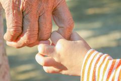 Close up asian grandmother and grandchild holding hands stock photo