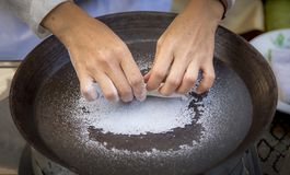 Asian hand making dessert from sugar icing on hot pan. stock photos