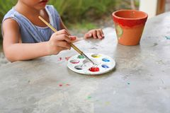 Close-up Asian kid girl paint on earthenware dish.  stock images