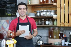 Close up asian man barista smiling holding laptop checking orders and stock behind the counter. cafe owner standing in restaurant royalty free stock images