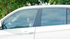Close up of Asian man driving a car to a stop outdoor stock footage