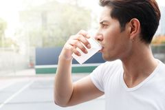 Man drink water. Close up asian man holding and drink a cup of water after exercise stock photography