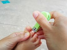Close-up Asian Mother cutting baby`s foot fingernails with nail Stock Photos
