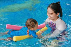 Close-up Asian mother teaching baby boy in swimming pool with noodle foam.  stock photos
