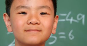 Close-up of Asian schoolboy standing against chalkboard in a classroom at school 4k. Close-up of Asian schoolboy standing against chalkboard in a classroom at stock video footage