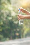 Close up Asian woman hand holding bottle of water on nature back Stock Image
