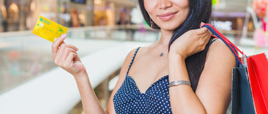 Close-up of asian woman's hand holding credit card and bags Royalty Free Stock Photography