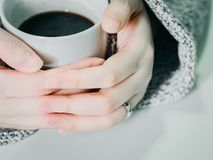 Close up asian woman 30s to 40s hand with cloth hold the white. Hot coffee cup from hand warming and drink on morning time with soft focus background Stock Images