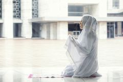 Asian woman praying for Allah in the mosque. Close up of Asian woman wearing prayer clothes while praying for Allah in the Istiqlal mosque stock image