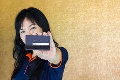 Close up Asian woman presenting back of debit or credit card with blank signature area Royalty Free Stock Photo