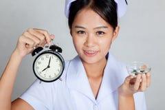 Close up Asian young nurse with clock and pills Stock Photo