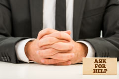 Close up Ask for Help Text on Small Wooden Piece. In Front Businessman with Crossed Hands on White Table Stock Photo