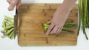 Asparagus. Woman Cuts Asparagus on a Wooden Cutting Board Close Up, Directly from Above. Close Up of Asparagus on a Cutting Board on White Background, Woman stock footage