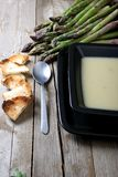 Close up of asparagus soup and black flat piece of Royalty Free Stock Images