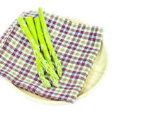 Close up Asparagus on table cloth in wooden plate Royalty Free Stock Photography