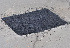 Close up on asphalt  road repair. Repair pavement and laying new Royalty Free Stock Image