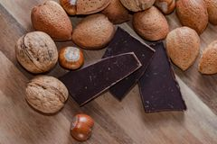 Close up of assorted nuts and pices of chocolate on a wooden tab royalty free stock image