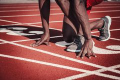 Close-up of the athlete`s hand and foot plan push off the track at the stadium Stock Photos