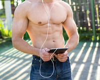 Close-up of an athlete stands on the site, listening to music, sexy, inflated bodybuilder, fashion style urban life Stock Photos