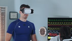 Close-up of athlete in VR glasses walking on racetrack during stress test. And his doctor is also in virtual reality goggles. In Scientific Sports Laboratory stock footage