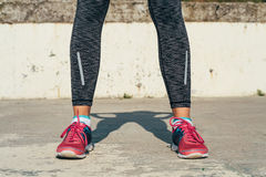 Close-up of athletic female legs in red sneakers on a concrete p. Ad outdoors in sunlight Stock Images