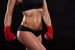 Close up athletic girl posing in red bandages, isolated on the dark background boxing fighter kickbox Stock Image
