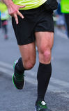 Close up athletic legs of man running. Victory sign Stock Photo