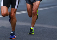 Close up athletic legs of two mans running Stock Photos
