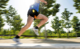 Close up athletic legs of young man running in city park on summer training in healthy lifestyle concept Stock Image