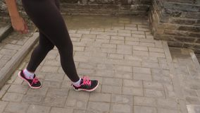 Close Up Of Athletic Female Legs Jogging Down The Stairs. Close-up, the athletic legs of a young woman run down the steps to the bottom. In tight black leggings stock video footage