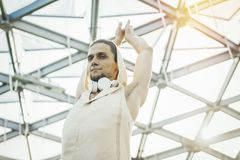 Close up of athletic man practicing yoga in modern park under the glass dome. Close up of attractive athletic man practicing yoga and warming up outdoors in royalty free stock photo