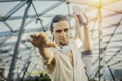 Close up of athletic man practicing yoga in modern park under the glass dome. Close up of attractive athletic man practicing yoga and warming up outdoors in royalty free stock images
