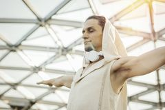 Close up of athletic man practicing yoga in modern park under the glass dome. Close up of attractive athletic man practicing yoga and warming up outdoors in royalty free stock photography